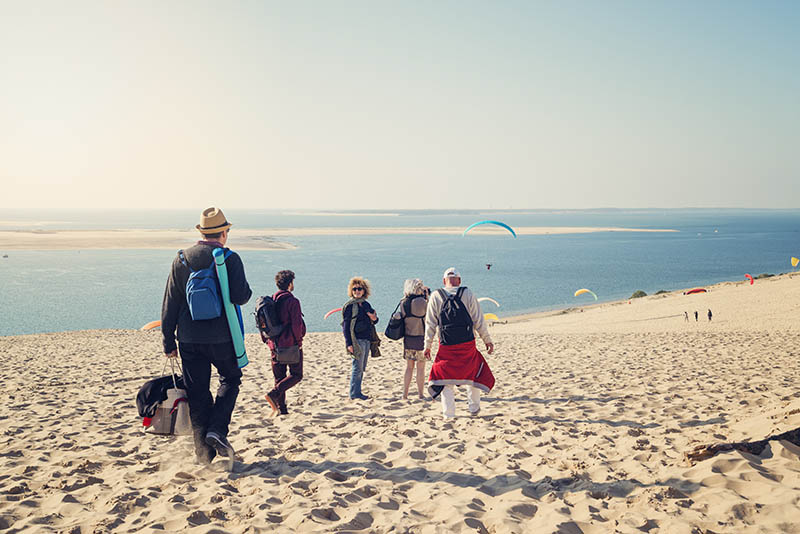 Group of friends walking on beach with warm clothes. Three men and two women, one young and four mature adults looking for a place to have a snack looking at the wonderful view. Horizontal full length outdoors shot with copy space. This was taken at the Dune du Pyla in France.