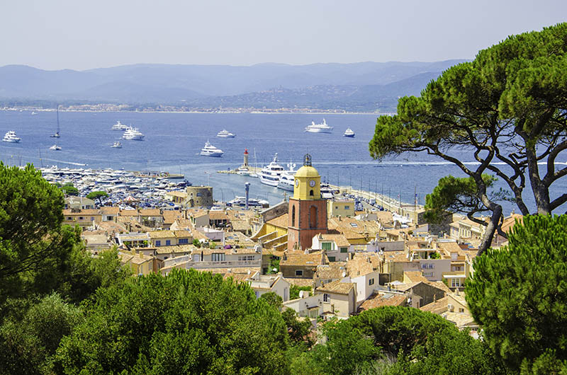 Looking from a viewpoint at the view of the town of Saint Tropez in France. St Tropez is a popular French summer holiday resort. The colour image was taken on a hot summer day. St.-Tropez is a coastal town on the French Riviera, in the Provence-Alpes-Côte d'Azur region of southeastern France. Long popular with artists, the town attracted the international
