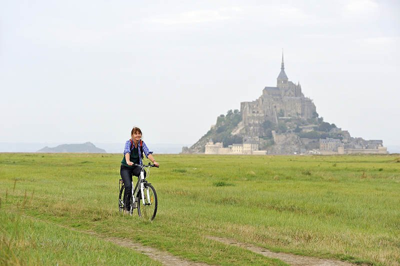 young woman cycling in the bay of Mont Saint-Michel, Manche department, Low Normandy region, France, Europe.