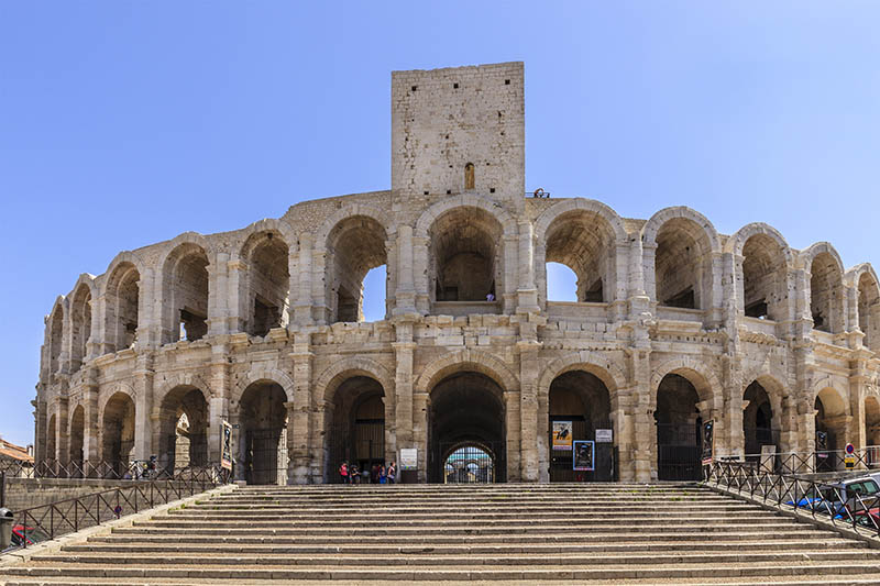 Arles, France - June 6, 2014: Tourists visiting the Roman Amphitheatre of Arles, one of the main sights of the city. Built in about 80 AD, the amphitheatre was capable of seating over 20,000 spectators, which attended the bloody hand-to-hand combats typical of that period.