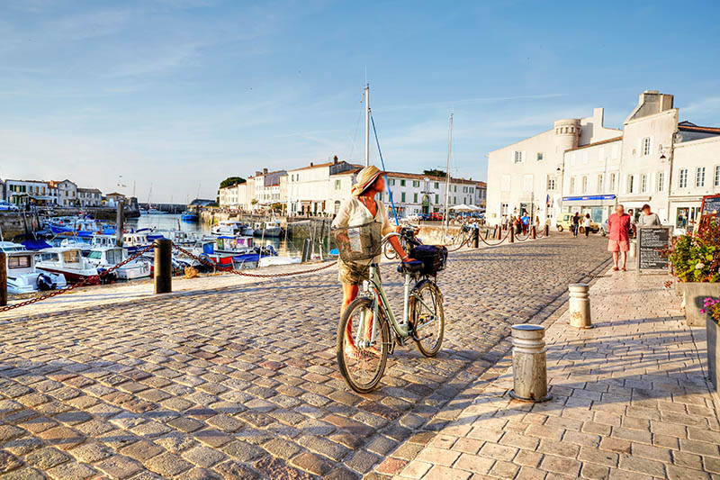 St. Martin-De-Re, France - June 25, 2015: Boats in harbour at St Martin-De-Re. Woman cycling on cobblestoned harbour at St Martin-De-Re. Other people are pictured walking in the background
