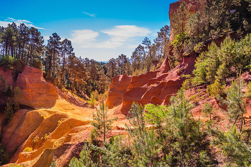 Scenic pit mining ocher - natural dyes. Roussillon, Provence Red VillageMulti-colored outcrops - from yellow to red-orange. Green trees create beautiful contrast from ochre. Roussillon, Red village of Provence