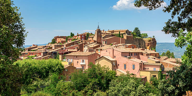 View to the idyllic village of Roussillon, famous for its large and colorful ochre deposits. Roussillon, Provence-Alpes-Cote d'Azur, France.