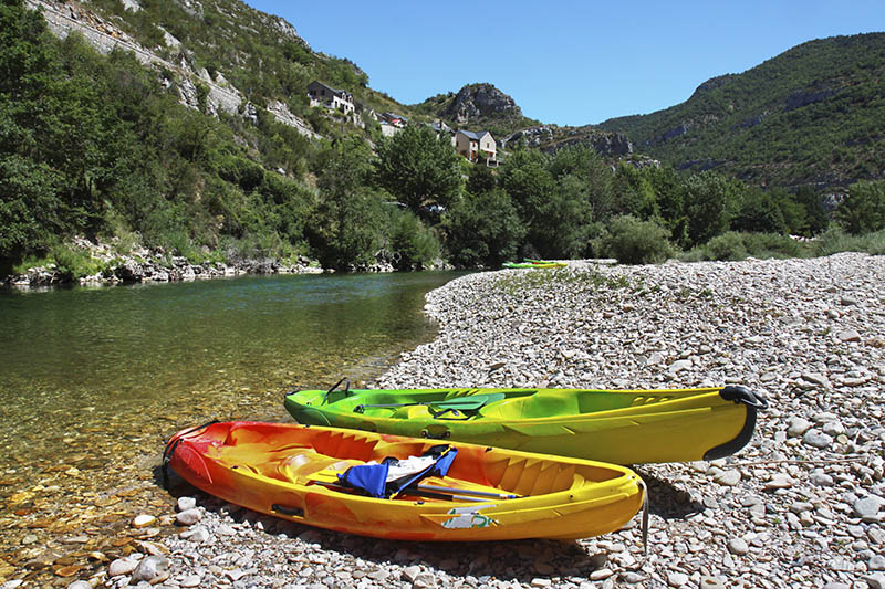 Two colorful canoes abandoned for a moment on the rocky banks of the river Tarn in the Gorges du Tarn in the South of France.