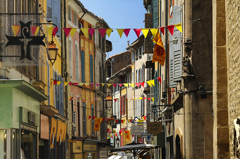Apt, France - June 17, 2005: Apt (Vaucluse, Provence, France): historic buildings and colorful flags.