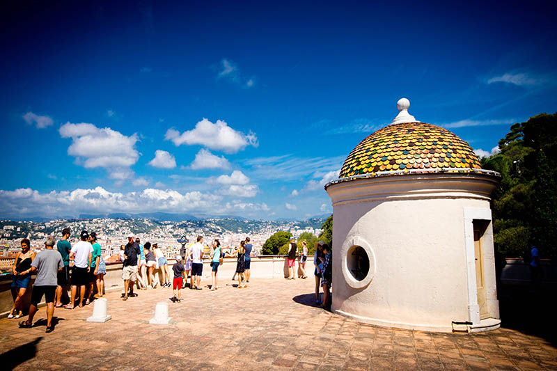 Nice, France - July 31, 2015: Castle Hill viewpoint at the Eastern end of the beach in Nice, France.  This is on a hot July summers day with many holiday makers and tourists on the patio looking at the view.