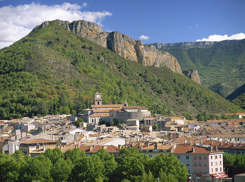 Houses and church with bell tower below a rocky hill at Digne les Bains, Alpes de Haute Provence, Provence, France, Europe