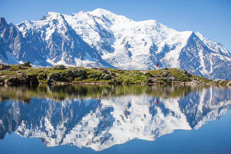 A trail runner in red runs along a crystal clear lake with the majestic Mont Blanc in the background. An almost perfect reflection is shown in the water of the lake.