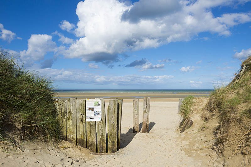 Utah Beach, Normandy, France - May 12, 2014: Entrance to Utah Beach, one of the D-Day landing sites on June 6, 1944, in Normandy, France. An informational sign is posted about the environmental life at the beach.
