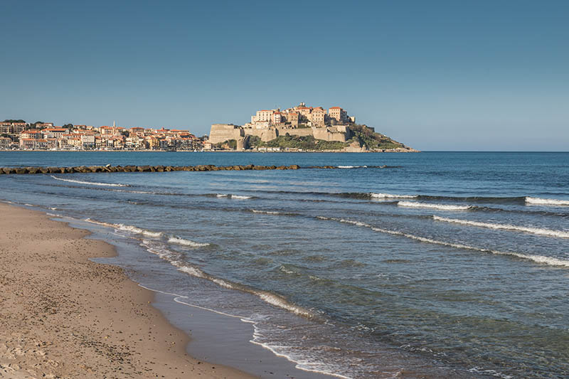 Waves gently lapping onto the sandy beach at Calvi with a view of the citadel and fortress in the distance along with the bars and restaurants around the harbour on a clear blue sunny day