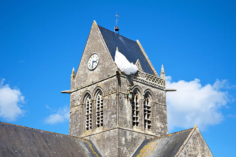 Belfry of the Church of Sainte-Mère-Église with the dummy of a soldier with the feat reminiscent parachute paratrooper John Steele who was suspended from the parachute, and spent two hours playing dead under fire until he could be released