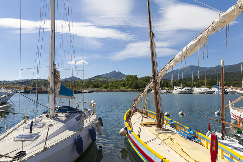 Harbor of Argeles-sur-mer with modern yacht and historic fishing boat in front. Mountain range of the Pyrenees in the background.