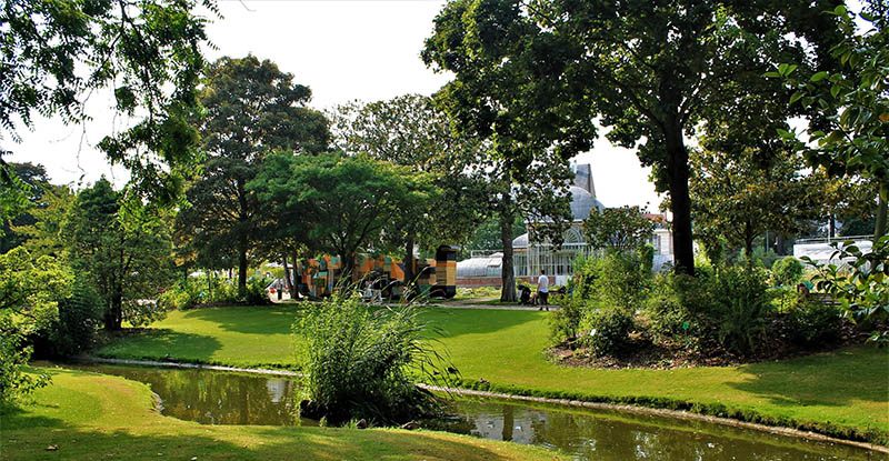 Nantes, France - June 22, 2017 : walk in the historical botanical garden of Nantes and view of the greenhouse in the background.