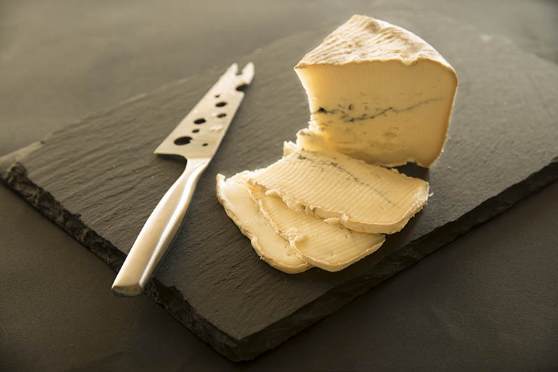 cheese on black slate platter and knife