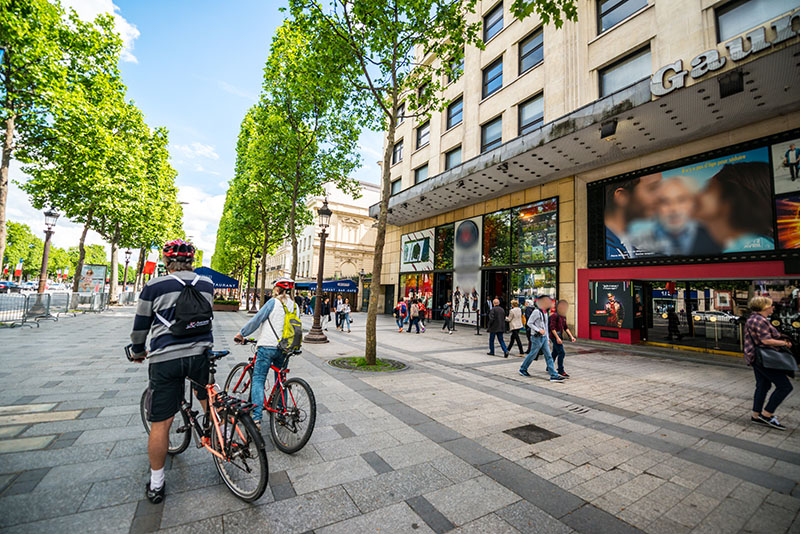 Paris, France - May 12, 2017: Tourists on bicycles on Avenue des Champs-Elysees, Gaumont movie theater on right side advertising new movie.